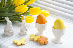 Easter decoration with yellow tulips, ceramic rabbits and colored eggs over light background Stock Images