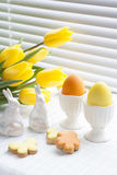Easter decoration with yellow tulips, ceramic rabbits and colored eggs over light background Stock Photos
