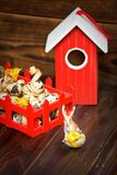 Easter decorations. Bunny with egg against red bird-house Royalty Free Stock Images