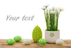 Easter decorations-  candle, eggs and flower in pot on the wooden background. Stock Photo