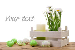 Easter decorations-  candle, eggs and flower in pot on the wooden background. Royalty Free Stock Photos
