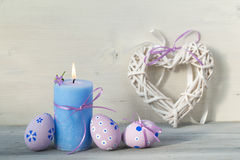 Easter decorations with easter eggs, burning candle and heart on a wooden background Stock Photo