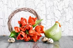 Easter arrangement with wooden wreath, red tulips, ceramic hen a. Easter decorations on gray rustic background. Arrangement with wooden wreath, red tulips stock images