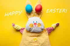 Easter decorations from a handmade toy rabbit and colorful eggs on an orange background. With the words happy Easter royalty free stock photos