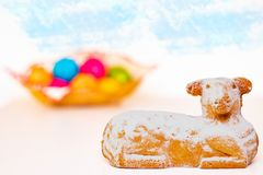 Easter decorations . Macro with focus on a traditional easter lamb or sheep cake on a bright table with blurred eggs in a stock images