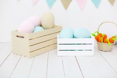 Easter decorations in pastel colors. In white room. Boxes with fabric eggs and carrot stock photo