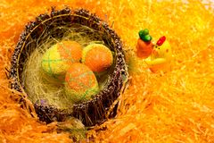 Easter decorations with some green eggs. Orange and yellow easter eggs in a basket on orange decorations stock image
