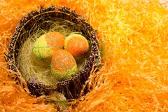 Easter decorations with some green eggs. Orange and yellow easter eggs in a basket on orange decorations royalty free stock photography