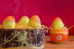 Easter decorations with some green eggs. Orange and yellow easter eggs in a basket on wooden table with some orange decorations stock photo