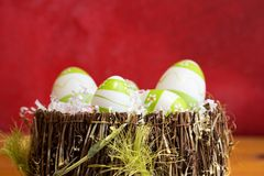 Easter decorations with some green eggs. Green and white easter eggs in a basket with red background royalty free stock photography