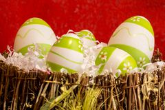 Easter decorations with some green eggs. Green and white easter eggs in a basket with red background royalty free stock image