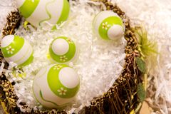 Easter decorations with some green eggs. Green and white easter eggs in a basket on white decorations stock photo
