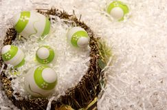 Easter decorations with some green eggs. Green and white easter eggs in a basket on white decorations stock images