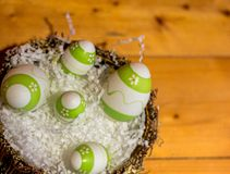Easter decorations with some green eggs. Green and white easter eggs in a basket on wooden table royalty free stock images