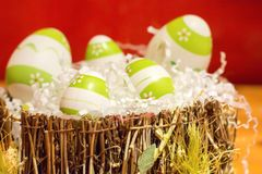 Easter decorations with some green eggs. Green and white easter eggs in a basket on wooden table with some white decorations stock images