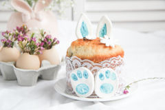 Easter decorations and treats. Easter cake in the form of the Easter Bunny and Easter decor with flowers on the table Royalty Free Stock Photo