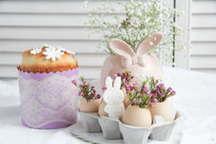 Easter decorations and treats. Easter cake in the form of the Easter Bunny and Easter decor with flowers on the table Royalty Free Stock Photos