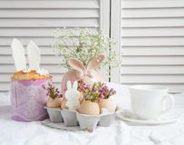 Easter decorations and treats. Easter cake in the form of the Easter Bunny and Easter decor with flowers on the table Stock Photos