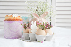 Easter decorations and treats. Easter cake in the form of the Easter Bunny and Easter decor with flowers on the table Stock Images