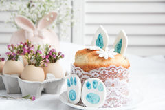 Easter decorations and treats. Easter cake in the form of the Easter Bunny and Easter decor with flowers on the table Stock Photo