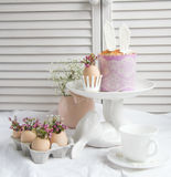 Easter decorations and treats. Easter cake in the form of the Easter Bunny and Easter decor with flowers on the table Stock Photography