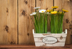 Easter decorations - wooden box with flowers  on the wooden background. Royalty Free Stock Photo