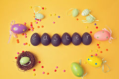 Easter decorations on yellow background.  Papier-mache eggs painted with chalkboard paint. View from above. Stock Photography
