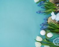 Easter decorative composition on a blue background. White rabbit, tulips, flower pots, unpainted eggs and a tree. View from above. Cozy composition. Easter Royalty Free Stock Photo