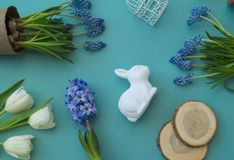 Easter decorative composition on a blue background. White tulips, flower pots, unpainted eggs and a tree. Easter decorative composition on a blue background Stock Images