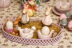 Easter decorative composition on a vintage background. Spring. A flowerpot with muscari flowers, a porcelain rabbits, eggs in the stock photography