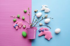 Top view of Easter eggs and handmade rabbits with spring green twigs on a pastel pink-blue background. Easter decorative rabbits and eggs with green spring Royalty Free Stock Photo
