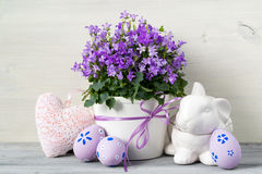 Easter design with easter eggs and a pot of flowers on a white wooden background. Easter design with easter eggs and a pot of purple flowers on a white wooden Royalty Free Stock Photos