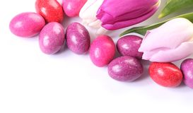 Easter detail. Close-up of chocolate eggs and tulips on white background royalty free stock photo