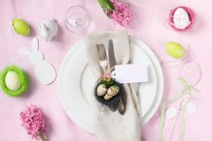 Easter dinner. Elegant table setting with spring flowers on pink tablecloth. Top view. Easter table setting with pink hyacinth flowers on pink linen tablecloth royalty free stock photo