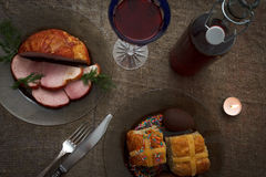 Easter dinner served on burlap tablecloth. Meat, hot cross buns, chocolate eggs and wine Royalty Free Stock Images