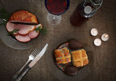 Easter dinner served on burlap tablecloth. Meat, hot cross buns, chocolate eggs and wine Stock Images