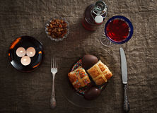 Easter dinner served on burlap tablecloth. Meat, hot cross buns, chocolate eggs and wine Stock Photos