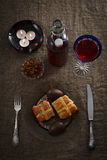 Easter dinner served on burlap tablecloth. Meat, hot cross buns, chocolate eggs and wine Royalty Free Stock Photography