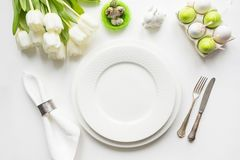 Easter dinner. Table setting with white tulip on table. Top view. Easter dinner. Table setting with white tulip, colorful eggs on white table. Top view. Space stock photo