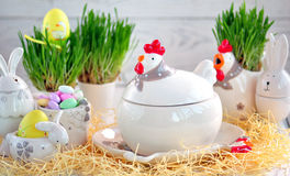Easter dishes in the form of chickens and rabbits on a white wooden background. Stock Photos