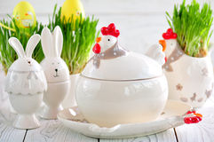 Easter dishes in the form of chickens and rabbits on a white wooden background. Stock Images