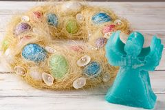 Easter DIY wreath with eggs and aroma candle, composition on rustic wooden table. Easter DIY wreath with eggs and aroma candle, composition on white rustic royalty free stock photo