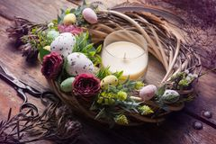 Easter DIY wreath with eggs and flowers. And aroma candle, composition on rustic wooden table royalty free stock photo