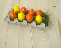 Easter. Easter eggs are yellow and orange. Eggs lie in the container for eggs. Green grass. Wooden background. Style eco. Rustic decor Stock Image