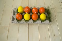 Easter. Easter eggs are yellow and orange. Eggs lie in the container for eggs. Green grass. Wooden background. Style eco. Rustic decor Royalty Free Stock Photography