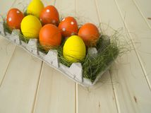 Easter. Easter eggs are yellow and orange. Eggs lie in the container for eggs. Green grass. Wooden background. Style eco. Rustic decor Stock Photography
