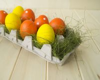 Easter. Easter eggs are yellow and orange. Eggs lie in the container for eggs. Green grass. Wooden background. Style eco. Rustic decor Stock Images