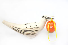 Easter egg. Painted yellow Easter Egg in a bird's beak on a white background Stock Image