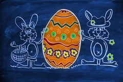Easter egg. Drawing on a blackboard, a pair of bunnies with a big smile Easter egg, made with colored chalks Stock Images