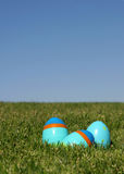 Easter Egg 2. Three plastic Easter eggs on the grass with a blue sky - shallow DOF stock photography